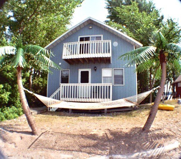 Lakeside with palm trees and a hammock on the beach and private decks