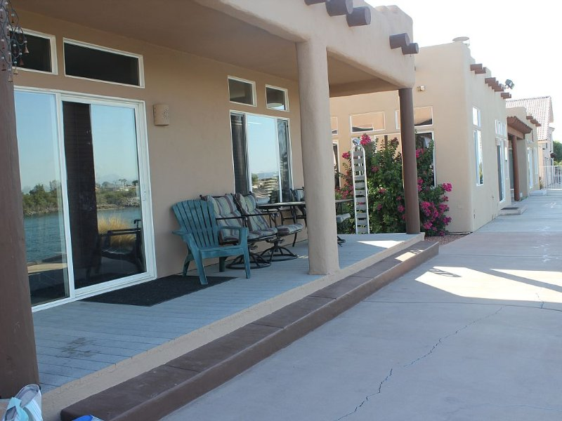 Rear patio area with table and chairs over looking the beach and river.