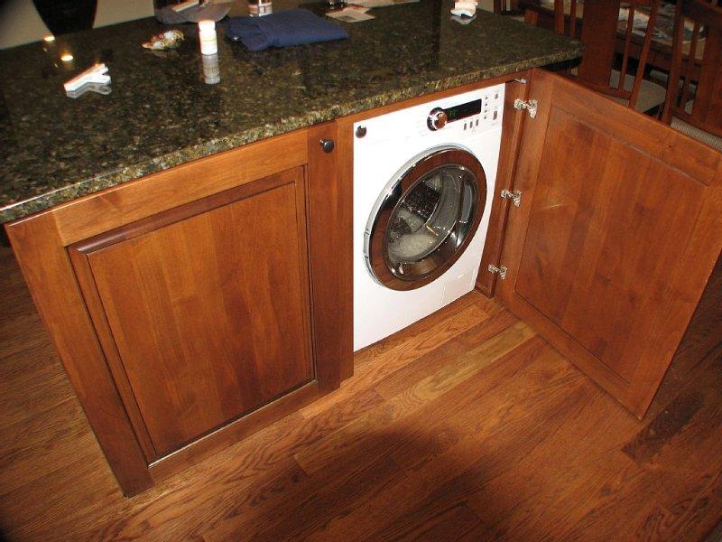 European style high efficiency front load washer/dryer under kitchen island.
