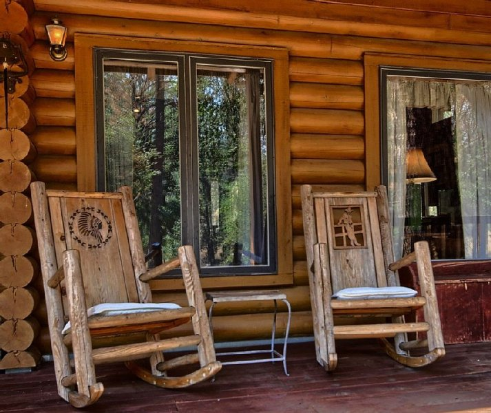 Front porch with custom hand-carved wooden rocking chairs.