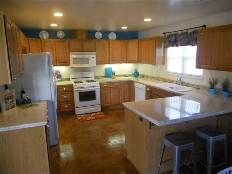 Fully Equiped Kitchen With New Appliances and Counter Seating.