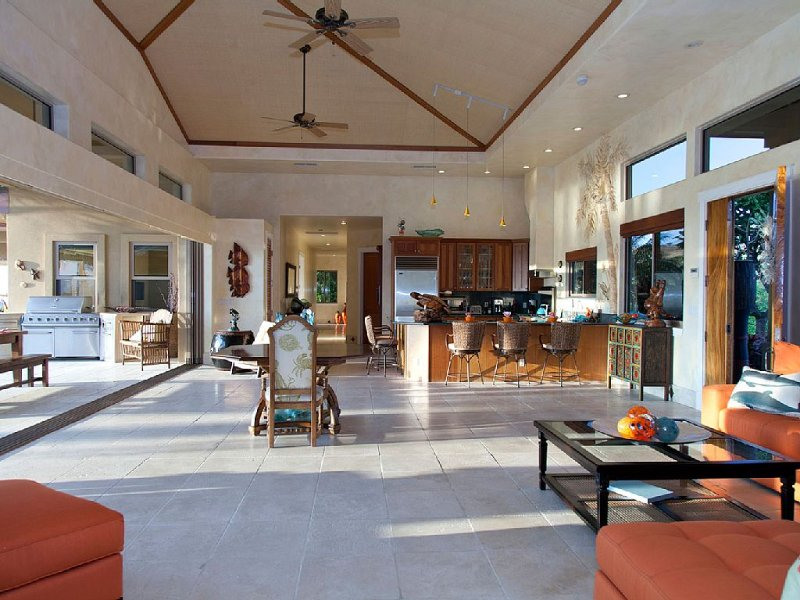 High ceilings in living room with oversized pocket doors to covered lanai.