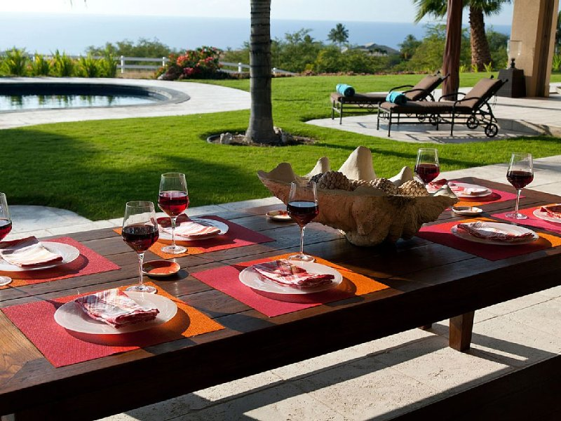 Outdoor dining under covered lanai with ocean and pool views.  Ideal climate