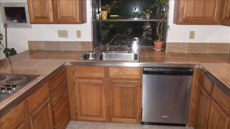 updated kitchen with granite tile countertop, dishwasher, oven & microwave