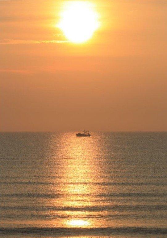 Nascer do sol sobre o barco de camarão