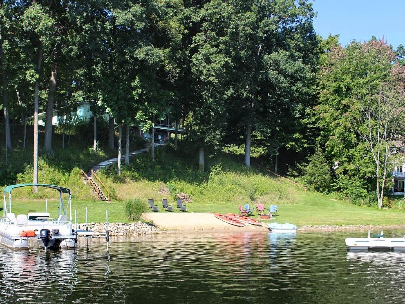 Sitting on a shady perch, the house overlooks a beach, yard, dock and raft.