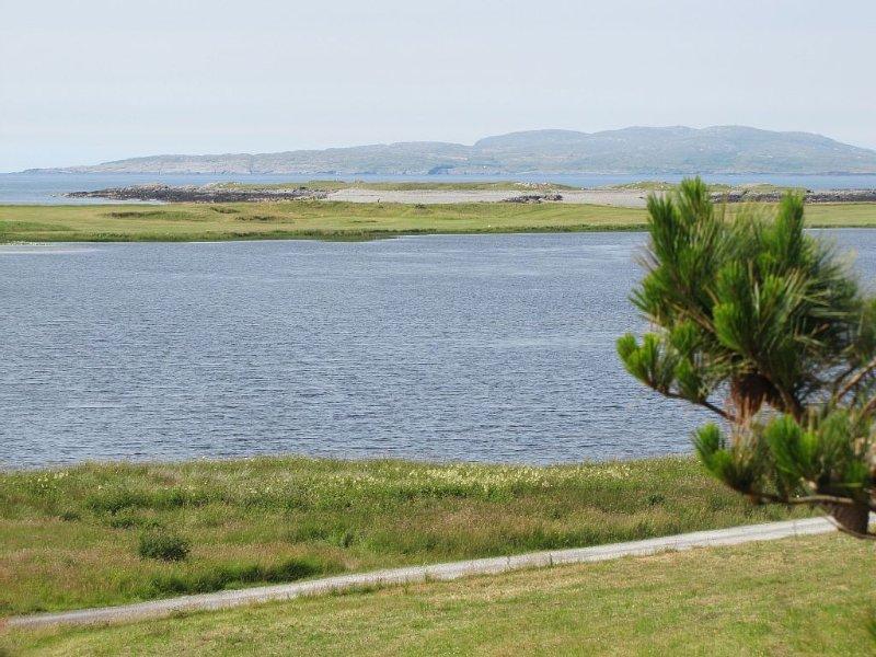 Vue de devant de la maison du lac, parcours de golf par 3, océan et île Inishturk.
