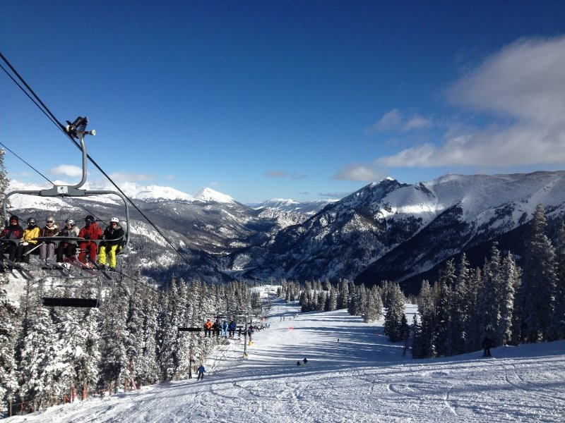 Skiers and boarders ride the lift up Copper Mountain on another bluebird day