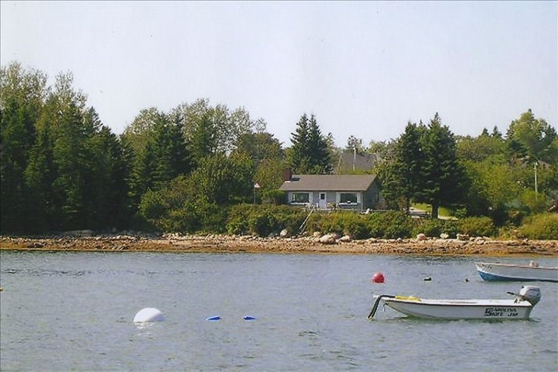 46 School St. from the water showing house, decks, woods, lawn, shoreline, steps