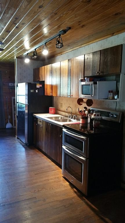 Cute kitchen with stainless steel appliances, double oven, and exotic wood cab.