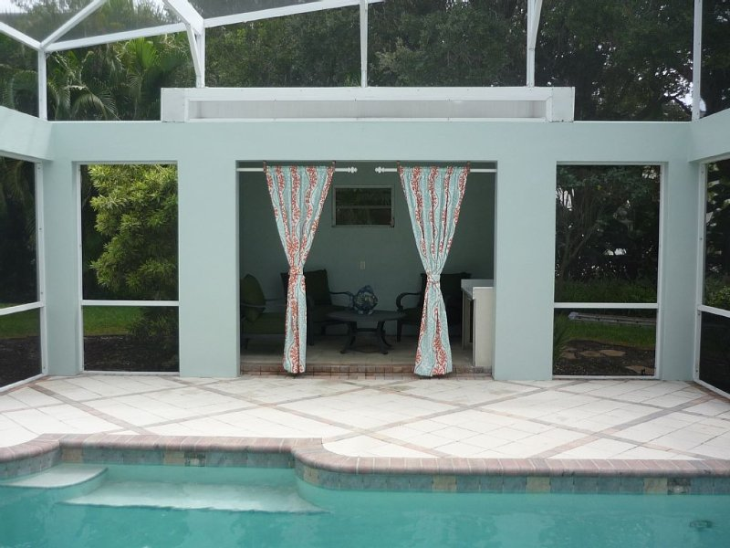 Poolside cabana with seating, sink and curtains for shade