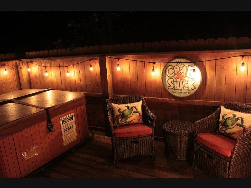 Romántico y festivo patio privado y bañera de hidromasaje en la noche.