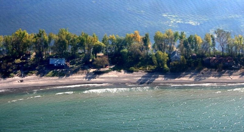 The beach and the cottage is the two structures on the right