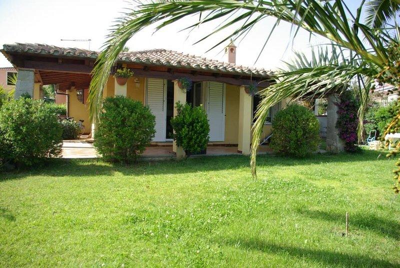 Villa con verande ombreggiate e giardino fronte mare.