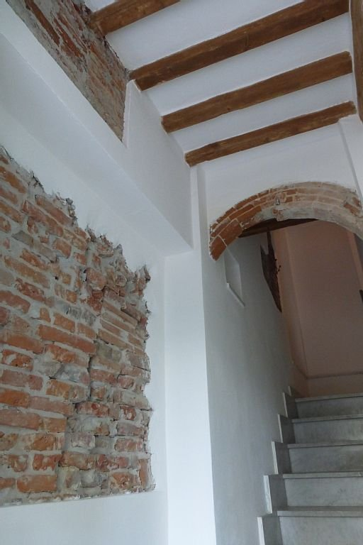 Particolare dell'ingresso con muri a vista ed arco
