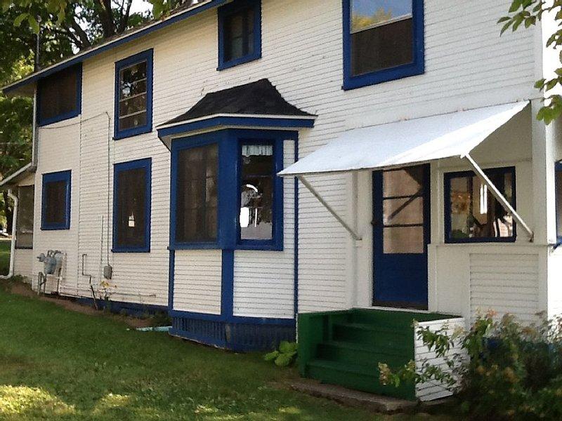 Lado norte de la casa, entrada exterior al porche, sala de estar, cocina, porche trasero.
