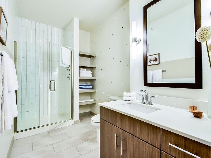 Full guest bathroom with frameless glass shower and plenty of towels.