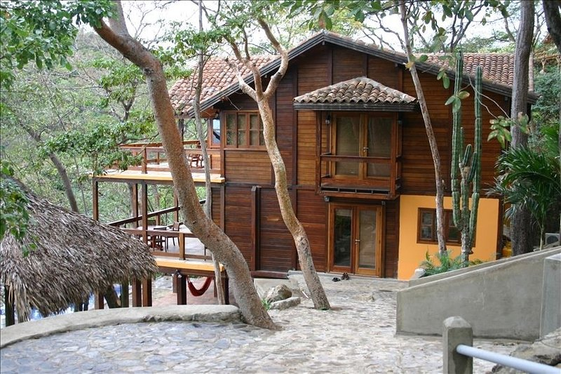 Exterior of home with the bay and palapa on the left and the casita to the right