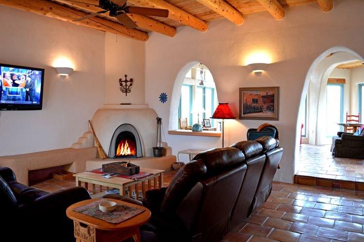 Living room large flat screen satellite TV & wood burning kiva fireplace