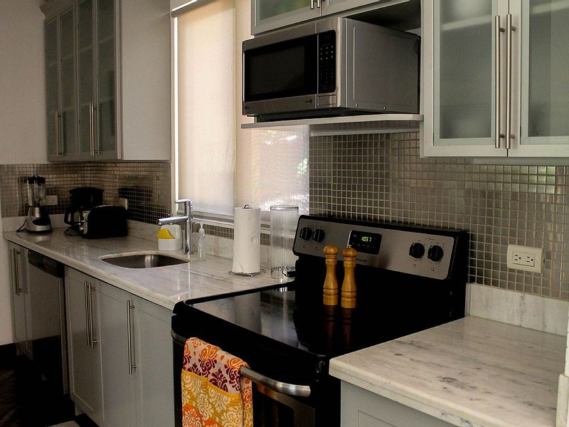 A full kitchen with stainless stell applicances with full size washer/dryer