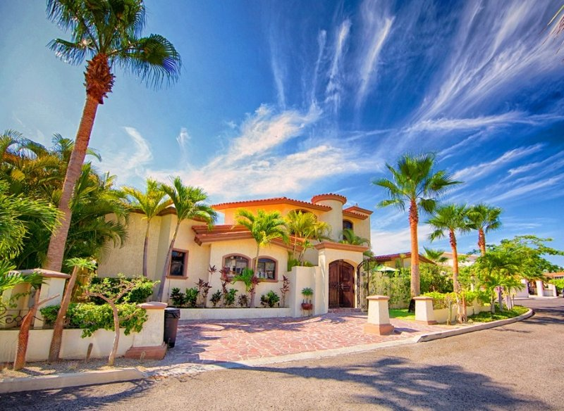 Front of Hacienda, lush landscaping, quiet street, parking in gated community