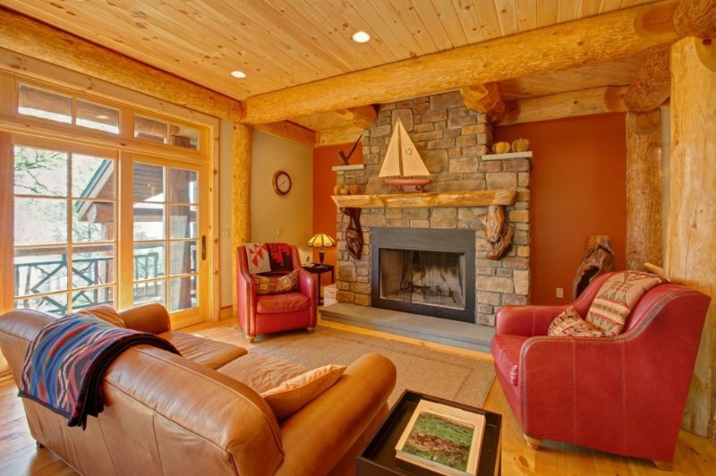 Wood burning fireplace in main- floor sitting area, leather couch, comfy chairs.