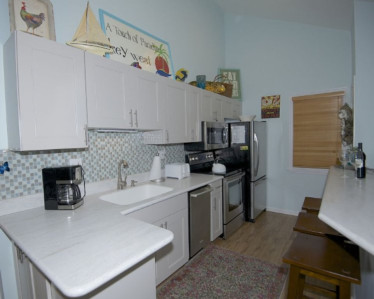 Kitchen with appliances breakfast bar and stools