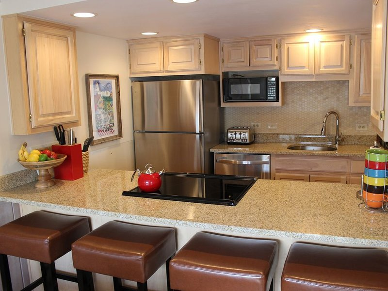 Updated Kitchen has granite countertops, tile, and stainless steel appliances.