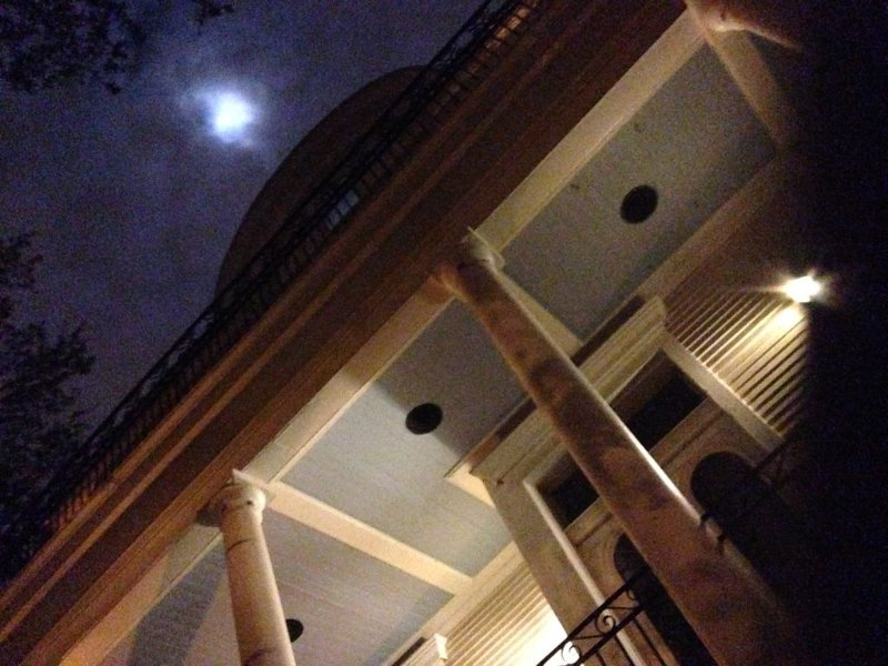 Looking up to the full moon with whispy evening skies, stately columns, lights