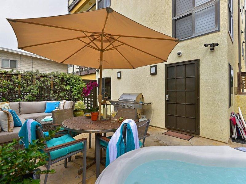 Patio privé avec bain à remous, terrasse et chaises longues. La plage est juste de l'autre côté du bâtiment.