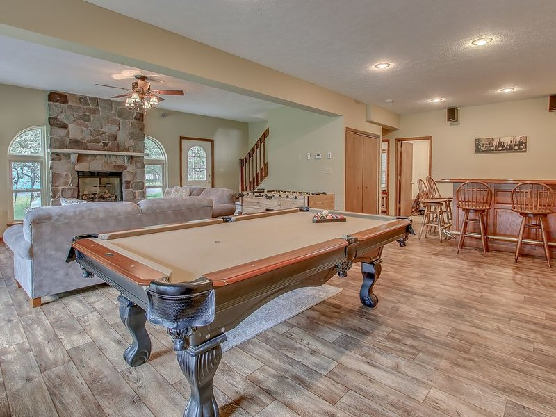 Great Room with Pool Table, Bar Counter, High Chairs, Couch, and Fireplace.