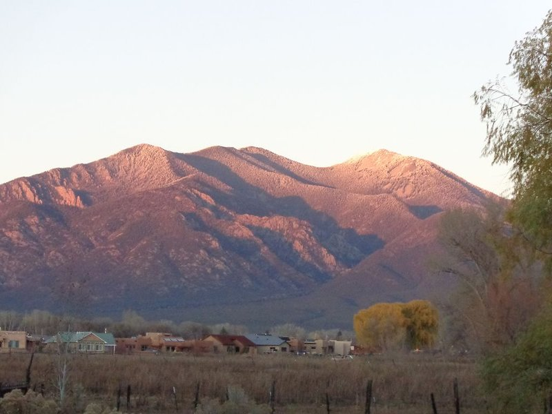 Across pastures spectacular view of Taos Mountain from the front of the property