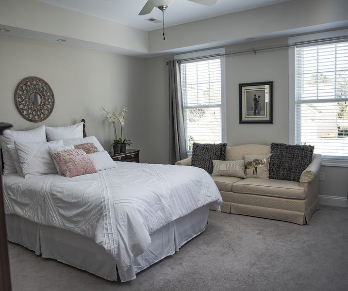 Spacious master bedroom with queen bed and tv