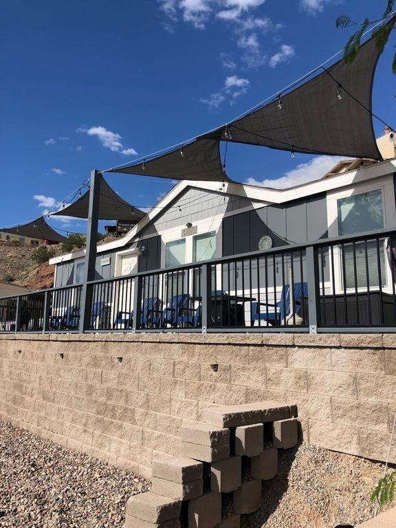Patio delantero con vista a las montañas y al río con estacionamiento adicional a lo largo de la pared frontal