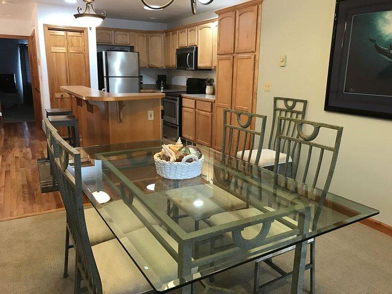 Belle table à manger en verre pouvant accueillir 6 personnes avec des sièges supplémentaires sur l'île.
