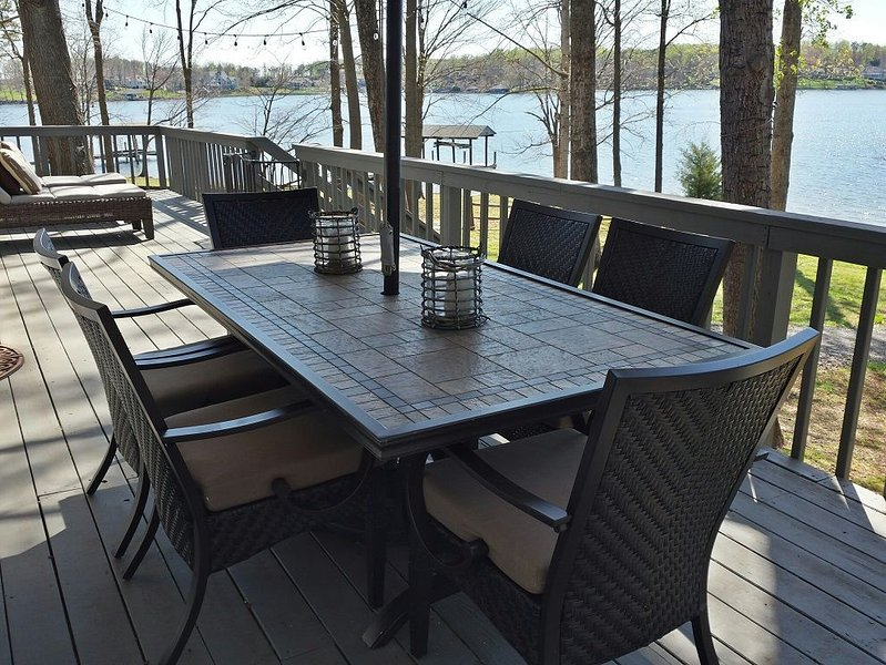 Large deck with comfortable seating, gas grill and wide water views