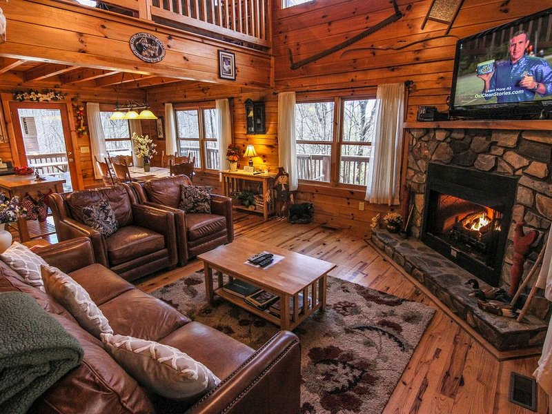 Living room with leather furniture, gas log fireplace and TV