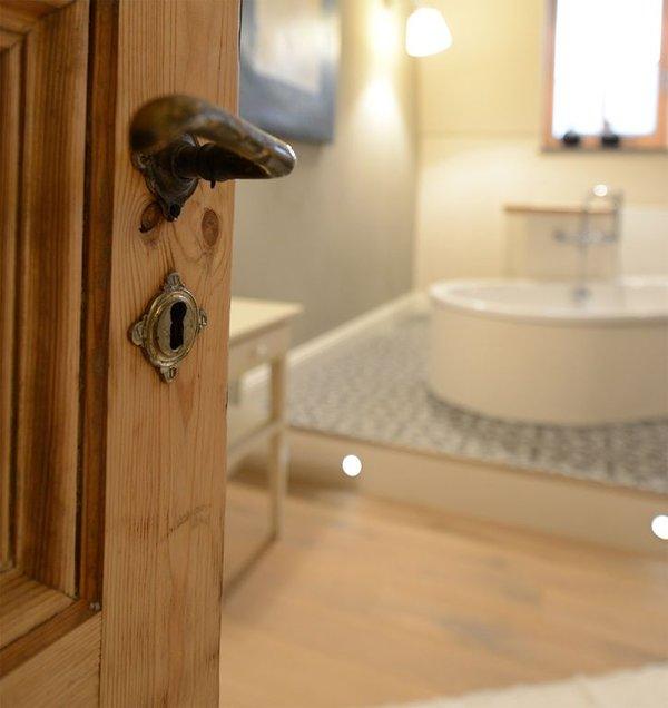 Una mirada al baño con sus antiguas puertas y hermosos pisos.