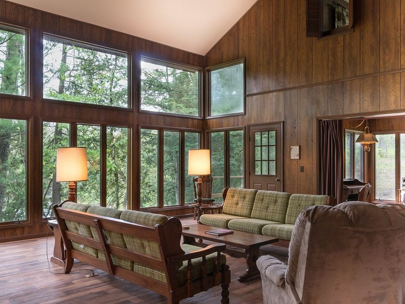 Huge open living area with soaring ceilings - Huge open living room space with soaring ceilings and lots of windows looking out to the Pere Marquette River.