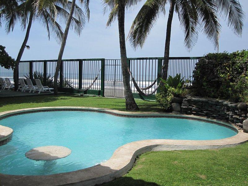 Vista a la piscina con vista al mar. Asientos en la piscina y mesa para el entretenimiento.