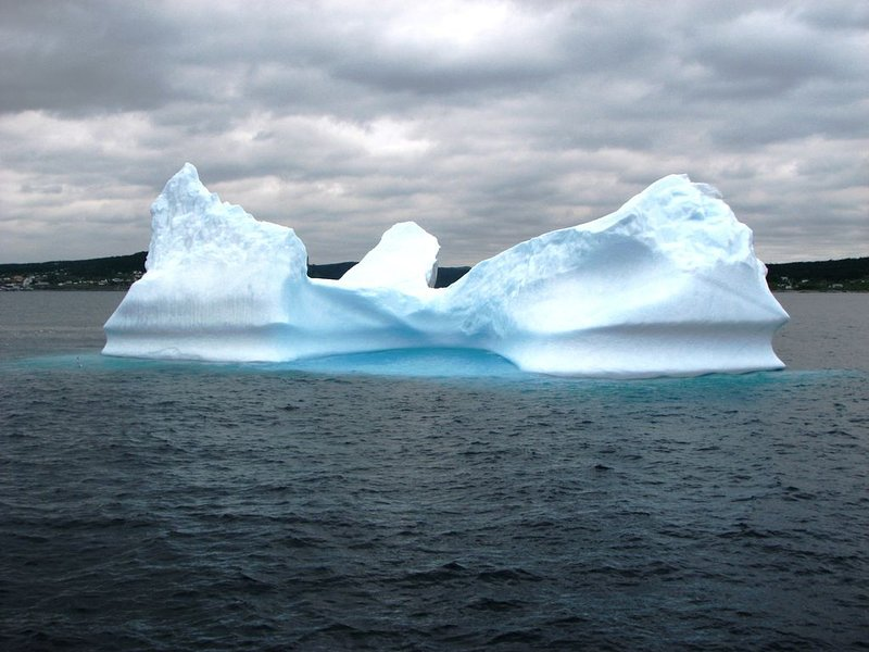 Mountainous icebergs tower out of the water, beautiful and imposing.