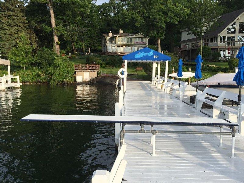 Muelle de natación con trampolín y entrada poco profunda a la orilla.