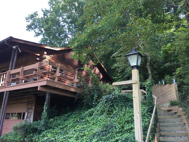 Façade de la maison avec des escaliers pour accéder au pont et au porche couvert.