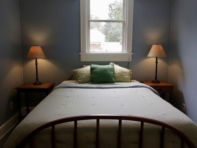 Cama queen size no quarto. Bambu cego para reduzir a luz da manhã.