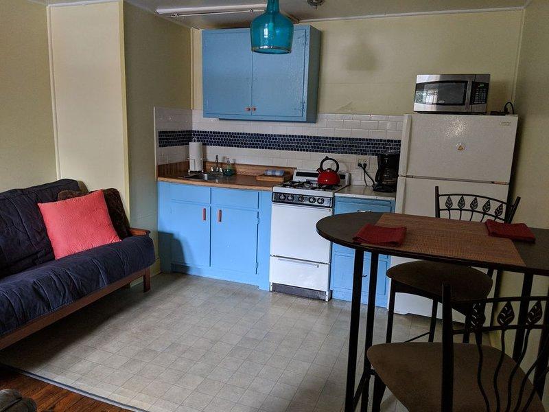 Cozinha urbana completa: fogão a gás, forno, microondas e geladeira grande.