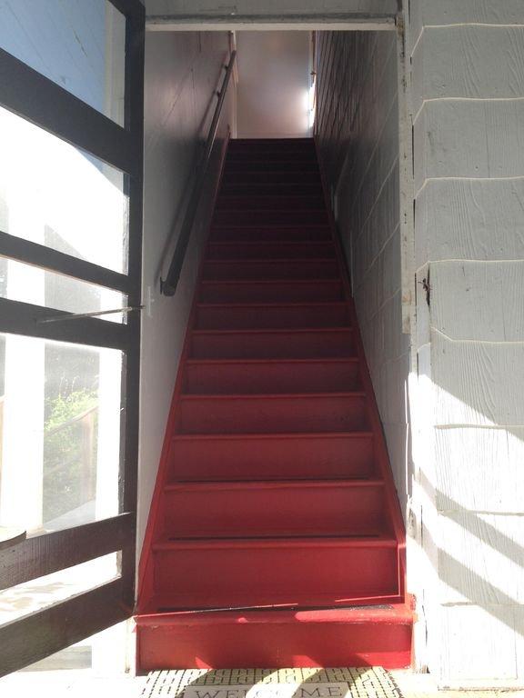 Escada fechada leva da varanda da frente para o apartamento. 20 passos.