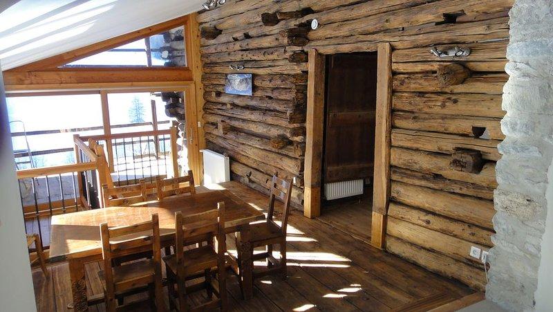 Le coin repas avec sa grande baie vitrée qui s'ouvre sur une terrasse couverte.