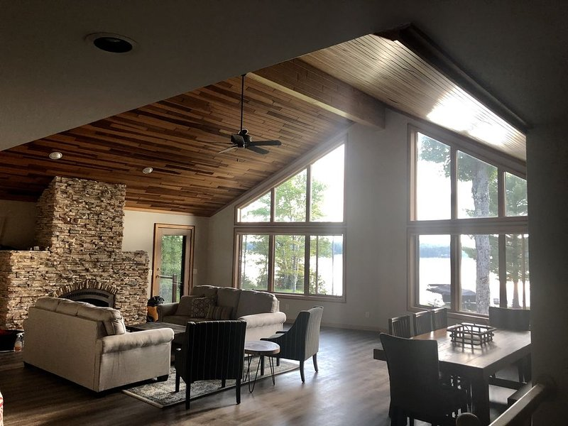 Large open main living area! Stone fireplace and windows overlooking the lake.