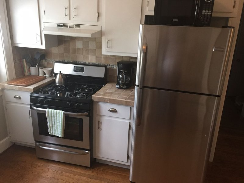 Kitchen with stainless appliances (gas range), coffee maker and tea kettle.