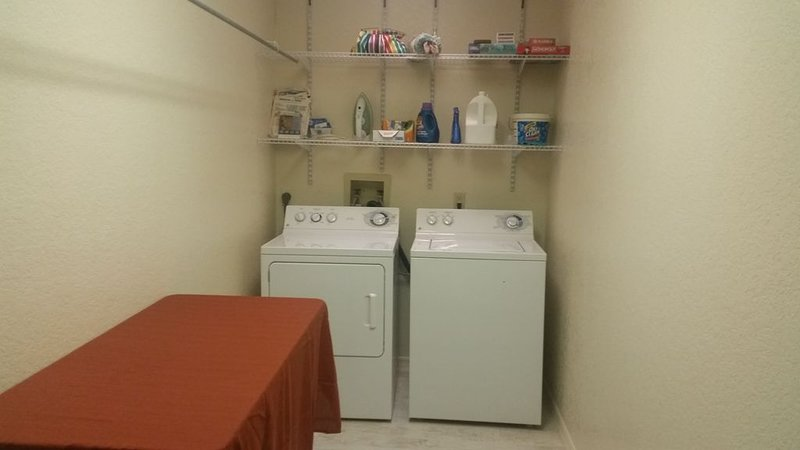 the laundry area with clothes hanging bar and folding table.